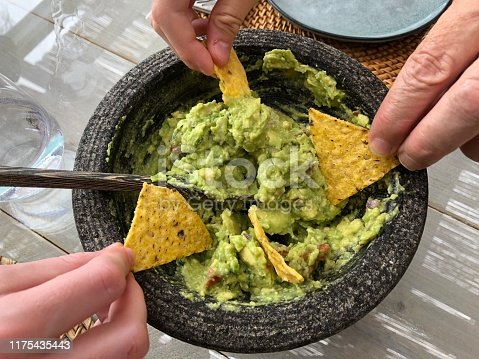 Three hands holding tortilla chips and dipping them in guacamole