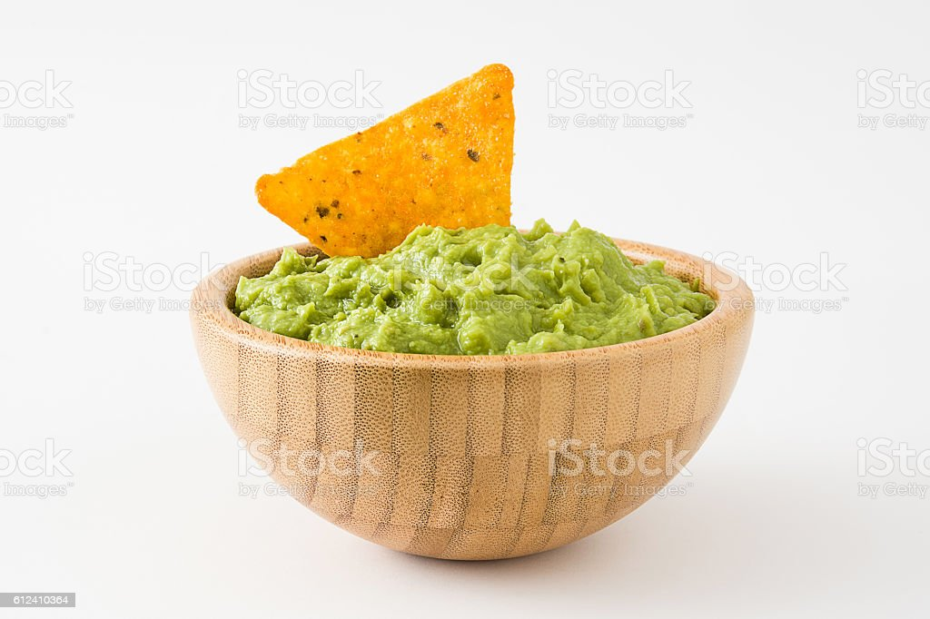 Guacamole in a wooden bowl and nacho stock photo