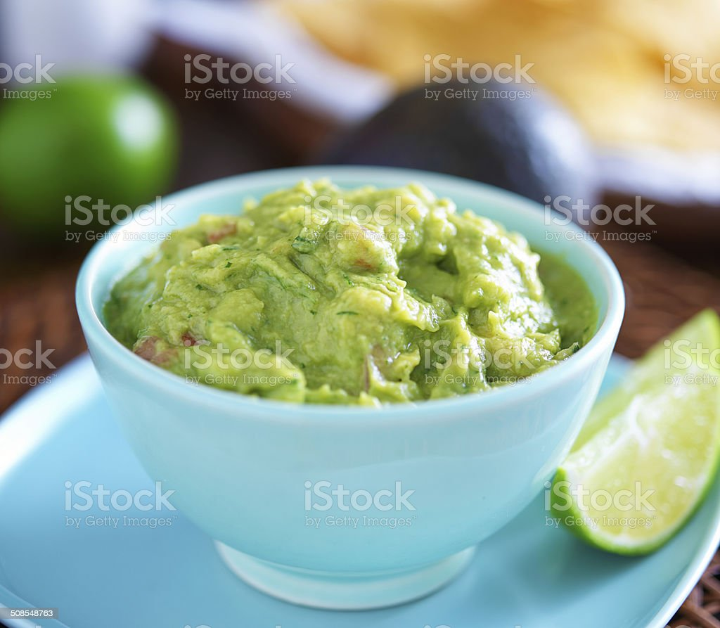 guacamole in colorful blue bowl with tortilla chips guacamole in colorful blue bowl with tortilla chips shot close up with selective focus Accuracy Stock Photo