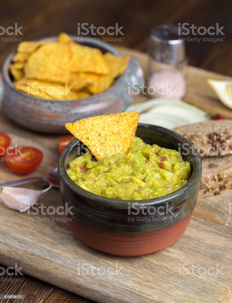 Guacamole in home crafted bowl on wooden desk. stock photo