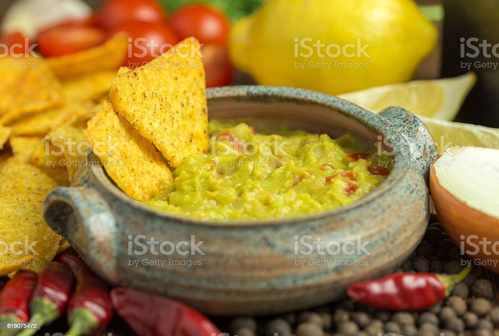 Guacamole in home crafted bowl with tortilla chips around. stock photo