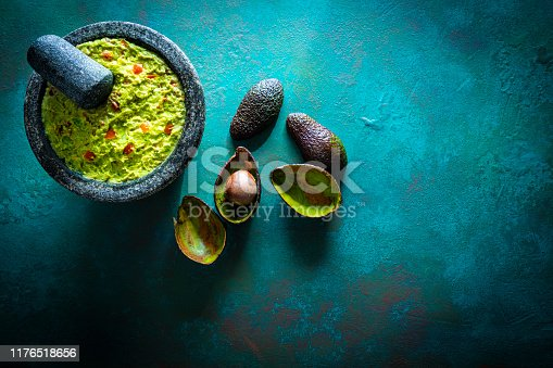 Guacamole prepared in molcajete with avocado on green grunge background