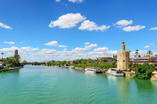 Guadalquivir River and the Golden Tower Guadalquivir River and the Golden Tower (Torre del Oroa in Spanish) of Seville is a military watchtower in Seville, Spain. It is located on the shore of the Guadalquivir River and the most emblematic symbols of Seville. It was built between 1220 and 1221 and one of the oldest buildings in Seville, Spain. seville stock pictures, royalty-free photos & images