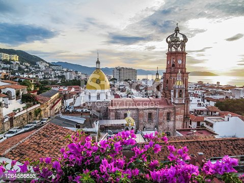 Famous Guadalupe Church with ocean and mountains in background framed with fuchsia buganvilla bushes in Puerto Vallarta Mexico.