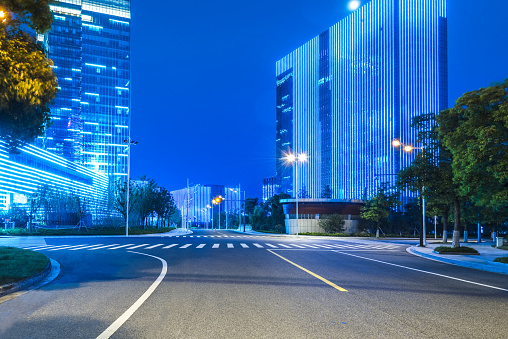 empty asphalt road and blue glass highrise at night.