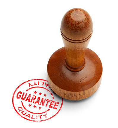 Red quality guarantee stamp with wooden stamper isolated on white background.