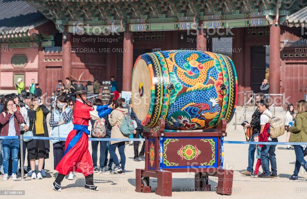 Guard beats large drum at Gyeongbokgung Palace stock photo