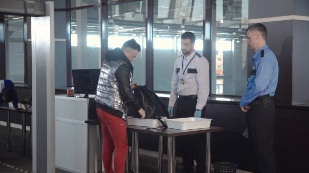 Guard checking passenger bag in airport Officer throwing away forbidden things out of passenger cabin baggage standing at counter in airport. security barrier stock pictures, royalty-free photos & images