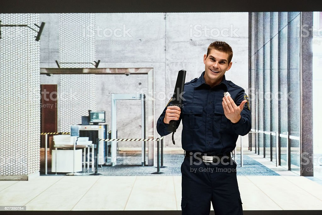 Guard holding a security wand and gesturing stock photo