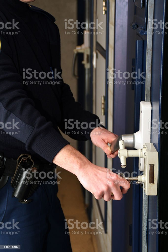 A guard locking up a cell door stock photo