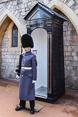 Windsor, United Kingdom - March 4, 2016: A guard outside Windsor Castle, close to the Guard house on the grounds inside the castle walls. The Guard is standing at attention and holding a rifle. Windsor Castle is one of the official residences of the British Royal Family