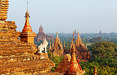 istock guard statue and Bagan temple field 154895094