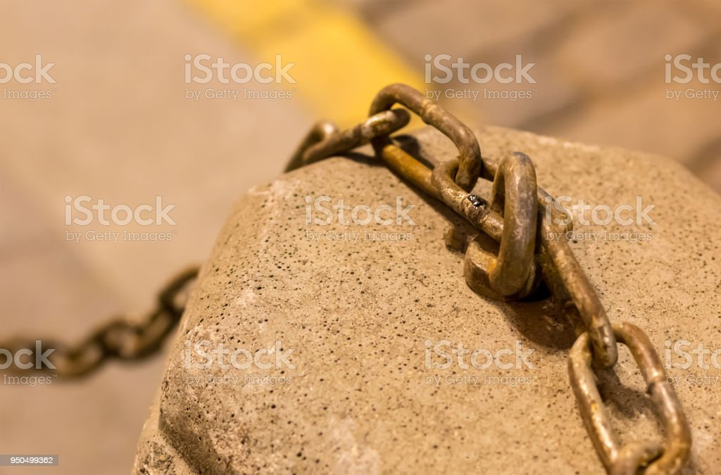 guard stone pedestal with an iron chain on a blurred background stone plaza, urban decor element stock photo