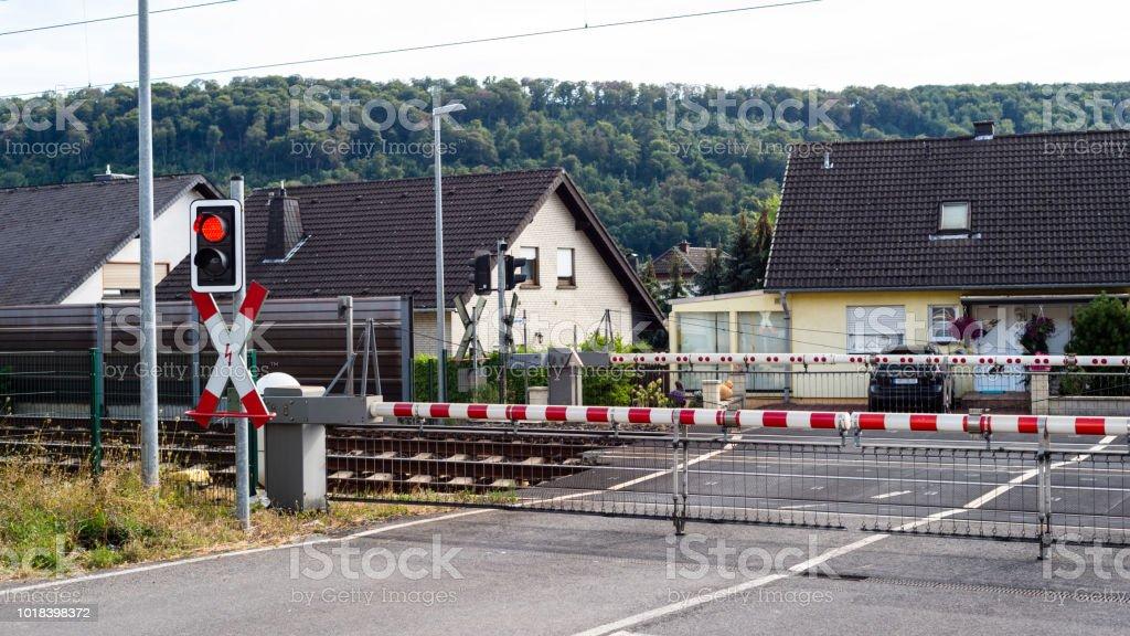 Ein bewachter Bahnübergang mit geschlossenen Schranken und ein rotes Licht. – Foto