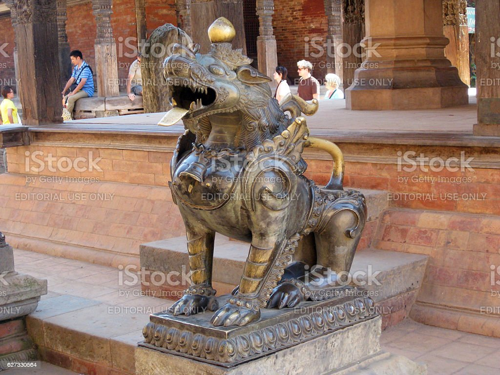 Guardian lion in bronze at a temple of Bhaktapur stock photo