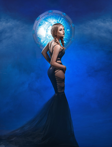Beautiful guardian of Portals standing in the center of the universe. Space style, hair and artistic make-up. Fantastic photo session. Fashionable toning