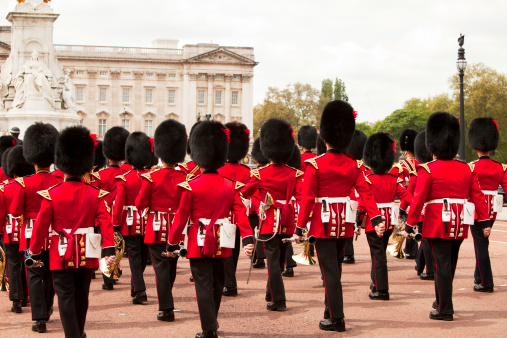 7 24 2019 London UK - British soldiers marching with trombones and trumpets during Changing of the Guard with tourists crowded at side of street watching. selective focus