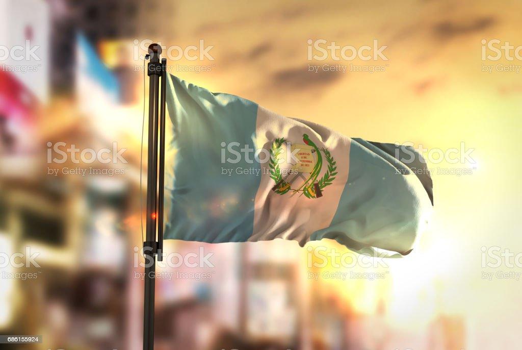 Bandera de Guatemala contra la ciudad borrosa de fondo en contraluz amanecer - foto de stock
