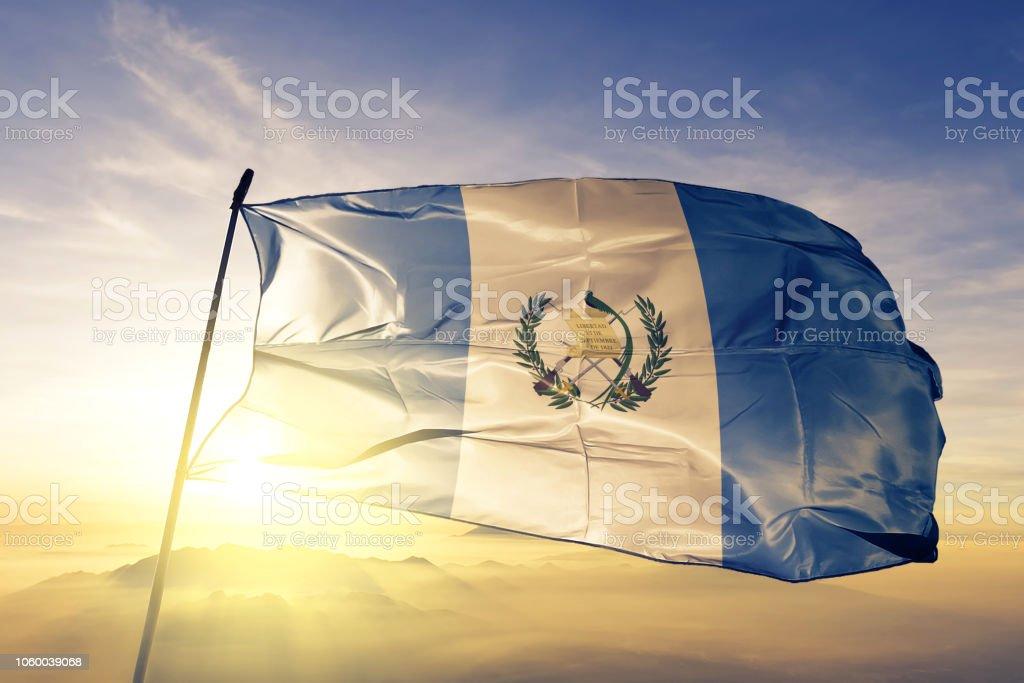 Guatemala Guatemala Guatemaltec bandera tela tela ondeando en la niebla de la niebla de amanecer superior - foto de stock
