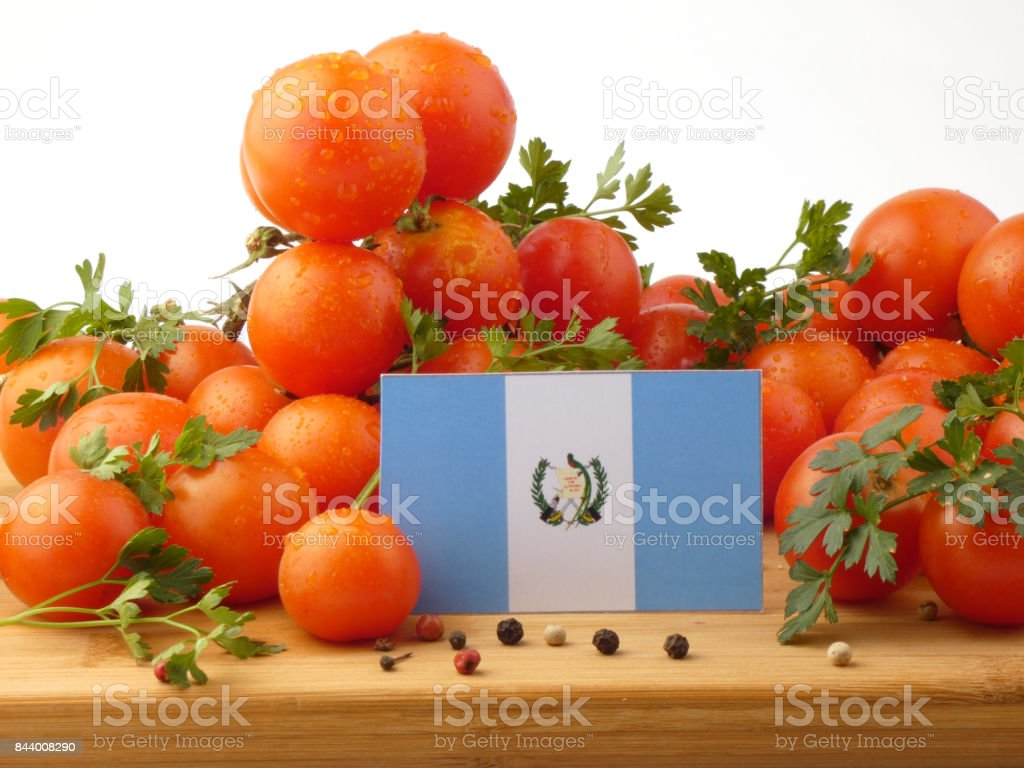 Guatemalan flag on a wooden panel with tomatoes isolated on a white background stock photo