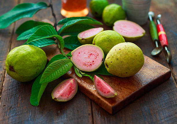 guava fruits ripe guava fruits and real guava tree leaves over wooden background. guava stock pictures, royalty-free photos & images