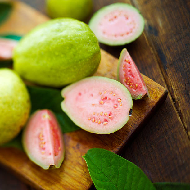 guava fruits ripe guava fruits on a vintage metal plate and knife guava stock pictures, royalty-free photos & images