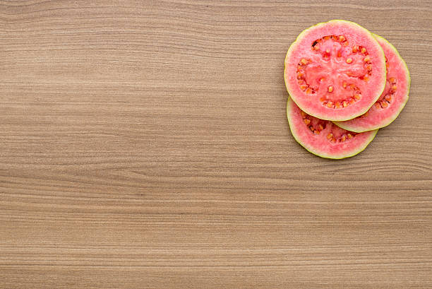 Guava Guava, refreshing red fruit for juice and healthy eating. Sliced fruit with wood background. guava stock pictures, royalty-free photos & images