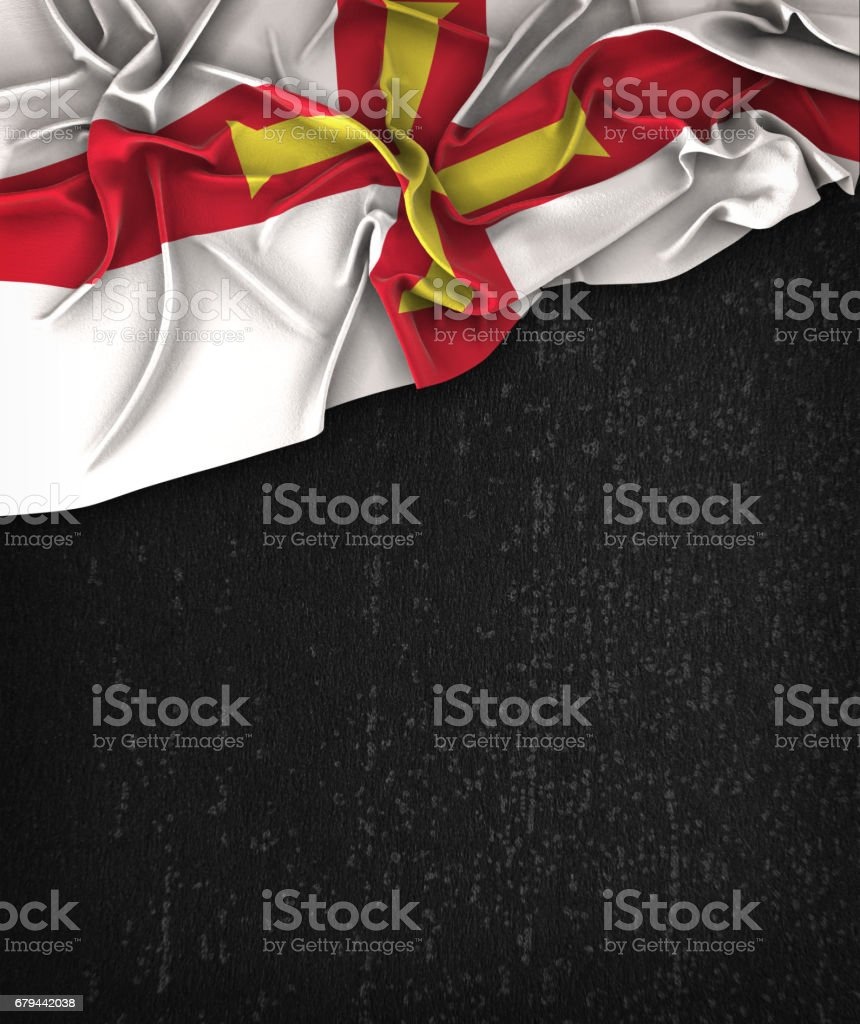 Guernsey Flag Vintage on a Grunge Black Chalkboard With Space For Text royalty-free stock photo