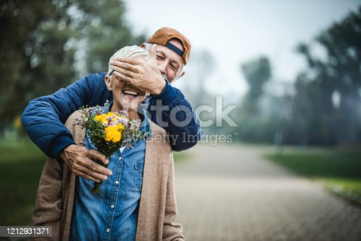 Happy senior man covering his wife's eyes while brining her flower bouquet at the park. Copy space.