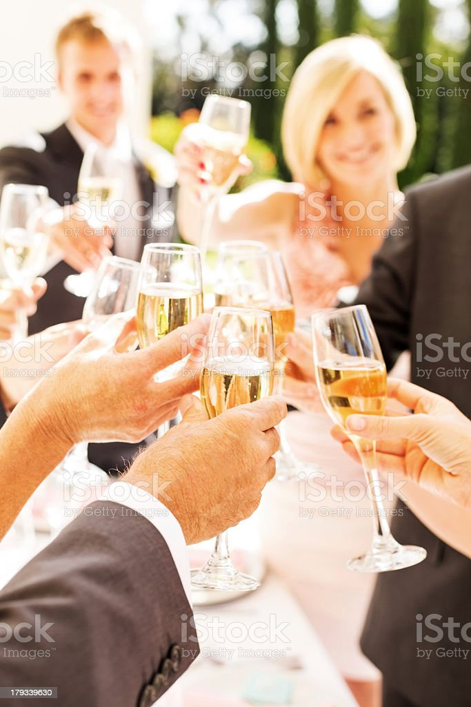 Guests And Couple Toasting Champagne Flutes During Reception stock photo