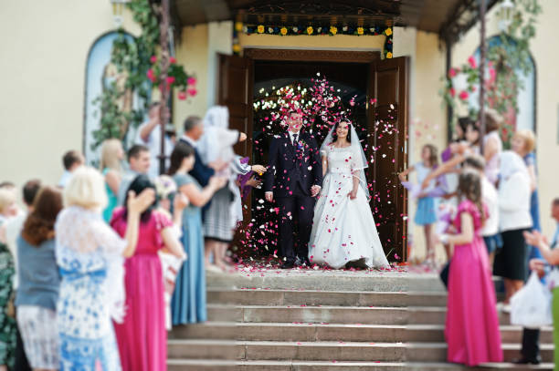 ゲストは教会からの出口でバラの花びらと結婚式のカップルを迎えています。 - 結婚式 ストックフォトと画像