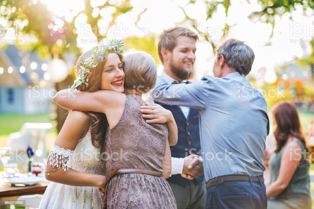 Hóspedes parabenizando a noiva e o noivo na recepção do casamento lá fora no quintal. - Foto de stock de Abraçar royalty-free