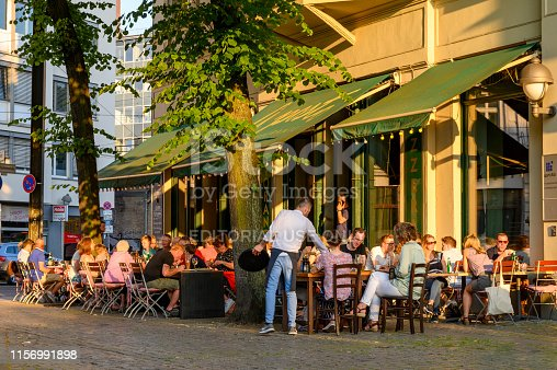 Berlin, Germany - June 17, 2019: Guests eating and drinking in a restaurant in the center of Berlin. The fully occupied tables and chairs stand on the sidewalk in the light of the setting sun.