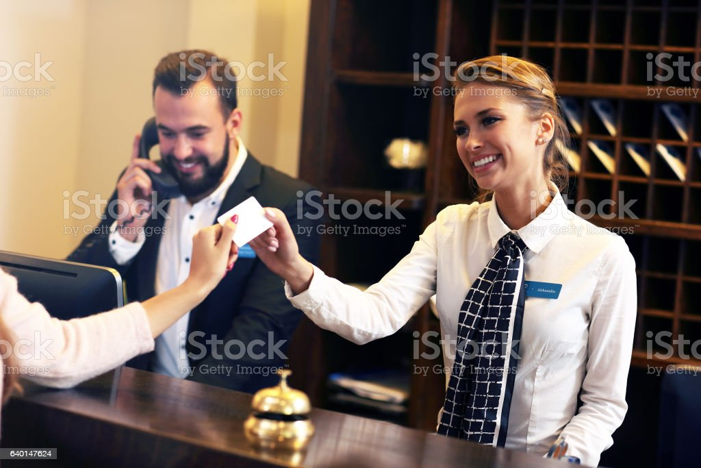 Guests getting key card in hotel​​​ foto