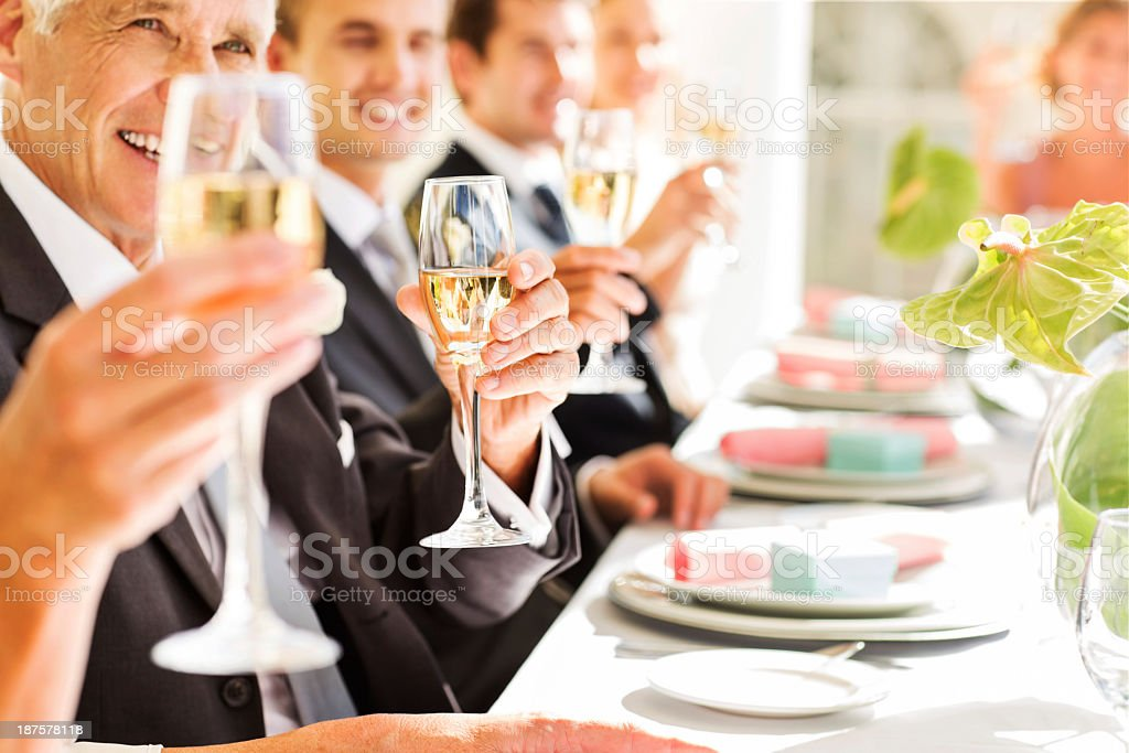 Guests Holding Champagne Flutes While Sitting At Table royalty-free stock photo