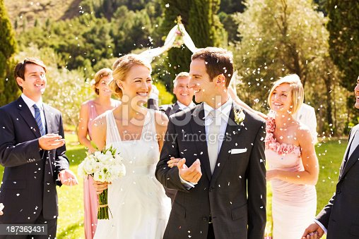 Happy wedding guests throwing confetti on newlywed couple after wedding ceremony in garden. Horizontal shot.