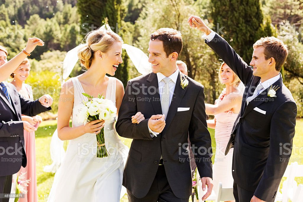 Guests Throwing Confetti On Couple During Outdoor Wedding stock photo