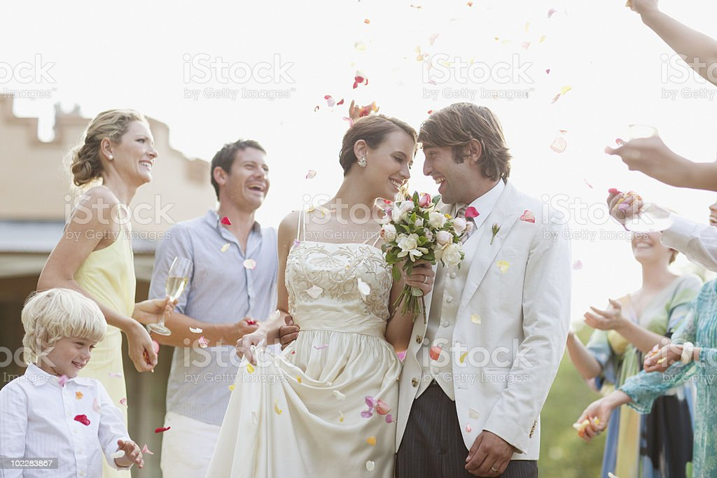 Guests throwing rose petals on bride and groom royalty-free stock photo