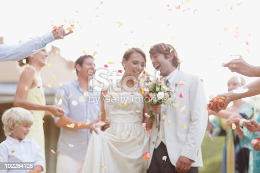 istock Guests throwing rose petals on bride and groom 102284126