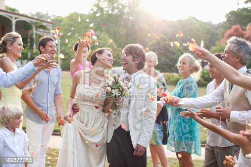 istock Guests throwing rose petals on bride and groom 169377083