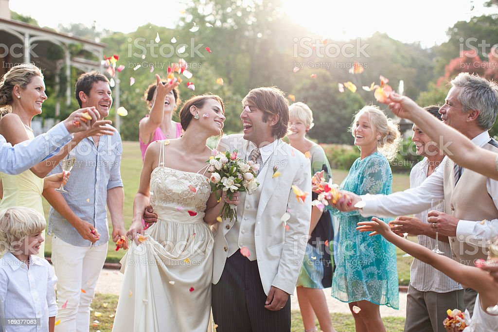Guests throwing rose petals on bride and groom stock photo