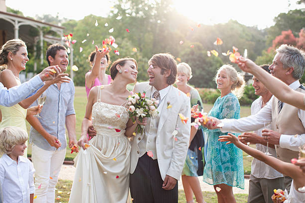 guests throwing rose petals on bride and groom - guest stock pictures, royalty-free photos & images