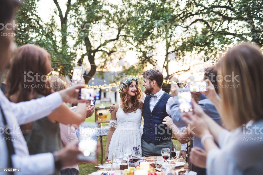 Gasten met het nemen van foto van bruid en bruidegom op de bruiloft receptie buiten smartphones. - Royalty-free Activiteit - Bewegen Stockfoto