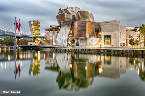 Bilbao, Spain - September 13, 2018: Reflection of the Guggenheim Bilbao museum and La Salve bridge on the Nervion river in Bilbao. The museum was designed by Frank Gehry