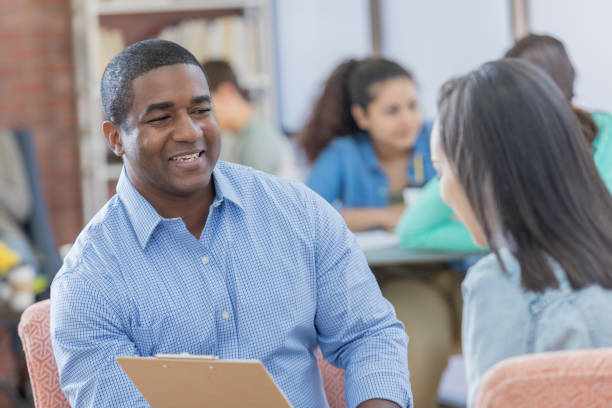 guidance counselor talks with female student - school counselor stock pictures, royalty-free photos & images
