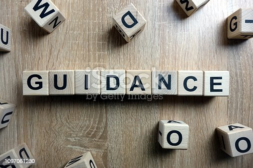 Guidance word from wooden blocks on desk