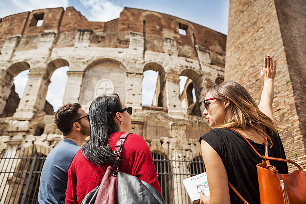 guide explaining to tourists the coliseum of rome - gids stockfoto's en -beelden
