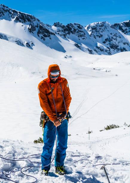 Führer, Instruktor und Bergretter, der vorstellt, wie man ein Seil an Simultettern und Gletscher anknüpft. – Foto