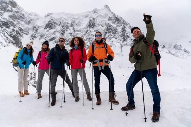 guide leading a group of people trekking in the alps - przewodzić zdjęcia i obrazy z banku zdjęć