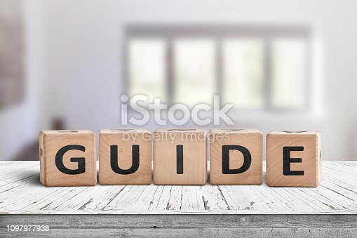 Guide sign made of wood on a desk in a bright room with windows